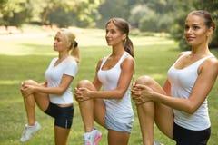 Класс фитнеса Красивые молодые женщины делая тренировку на PA лета Стоковые Фото