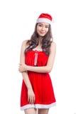 кладет женщину в мешки santa Девушка красоты азиатская модельная в шляпе Санты изолировала o Стоковая Фотография