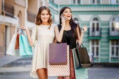 кладет счастливых женщин в мешки покупкы молодых Стоковые Изображения RF