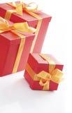 кладет тесемку в коробку красного цвета золота подарка Стоковое Фото