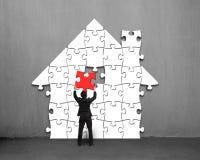 Кладущ красную головоломку в дом сформируйте на стене иллюстрация штока