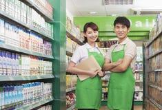 2 клерка продаж стоя в супермаркете Стоковое Фото