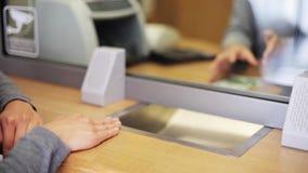 Клерк подсчитывать деньги и клиент на офисе банка видеоматериал