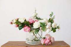 Клетка вполне розовых цветков на деревянном столе Стоковые Изображения