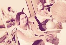 2 клиента женщин имея маникюр быть сделанным в салоне ногтя Стоковые Изображения