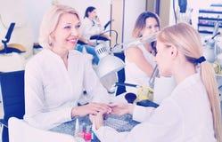 2 клиента женщин имея маникюр быть сделанным в салоне ногтя Стоковая Фотография RF