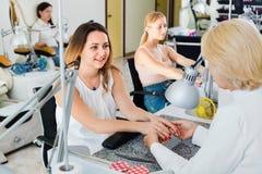 2 клиента женщин имея маникюр быть сделанным в салоне ногтя Стоковое фото RF