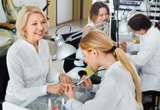 2 клиента женщин имея маникюр быть сделанным в салоне ногтя Стоковые Фотографии RF