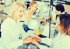 2 клиента женщин имея маникюр быть сделанным в салоне ногтя Стоковое Изображение