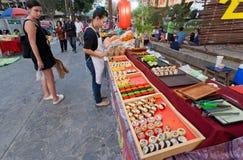 Клиенты еды, закусок и суш уличного рынка наблюдая с морепродуктами на суде фаст фуда Стоковое Фото