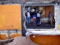 Клиенты на магазине увиденном до конца окну сокрушенного старого здания Стоковые Изображения RF