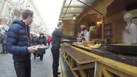 Клиенты покупают свеже испеченную еду от кашевара в внешнем шатре акции видеоматериалы