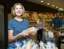 Клиенты покупая хлеб в продовольственном магазине Стоковое Изображение