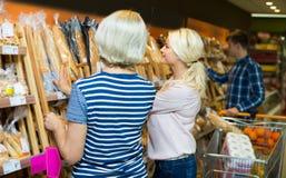 Клиенты покупая хлеб в продовольственном магазине Стоковые Изображения