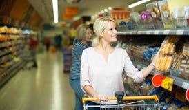 Клиенты покупая хлеб в продовольственном магазине Стоковая Фотография