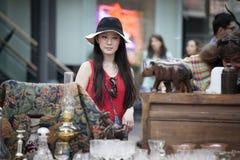 Клиенты смотря антиквариаты на стойле на рынке Spitalfilds стоковые изображения