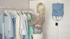Клиенты счастливой молодой моды красивые женские выбирая платья на магазине сток-видео
