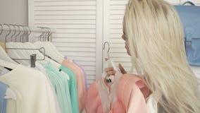 Клиенты счастливой молодой моды красивые женские выбирая платья на магазине акции видеоматериалы
