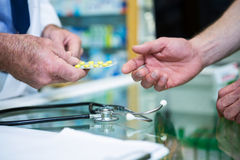 клиент давая аптекаря микстуры к Стоковые Фото