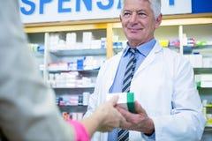 клиент давая аптекаря микстуры к Стоковые Изображения RF