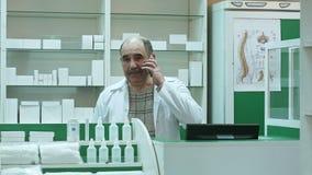 Клиент аптекаря советуя с через сотовый телефон в аптеке сток-видео