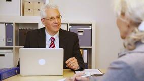 Клиент говоря к бизнесмену в офисе акции видеоматериалы