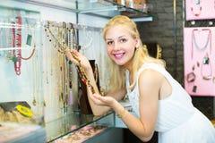 Клиент девушки выбирая ожерелье Стоковые Изображения RF