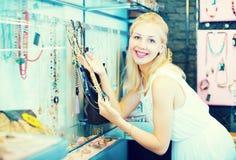 Клиент девушки выбирая ожерелье Стоковые Изображения
