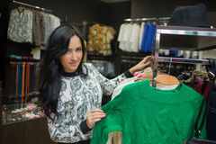 Клиент девушки выбирая рубашку в магазине одежды Стоковые Фото