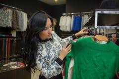 Клиент девушки выбирая рубашку в магазине одежды Стоковое Изображение RF