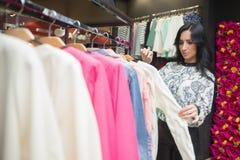 Клиент девушки выбирая рубашку в магазине одежды Стоковое Изображение