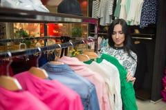 Клиент девушки выбирая рубашку в магазине одежды Стоковая Фотография