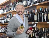 Клиент держа бутылки красного и белого вина в магазине Стоковое Изображение RF