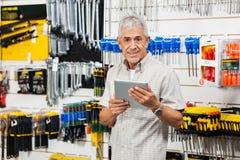 Клиент держа таблетку цифров в магазине оборудования Стоковое Изображение RF