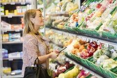 Клиент держа таблетку цифров пока смотрящ овощи Стоковые Изображения RF