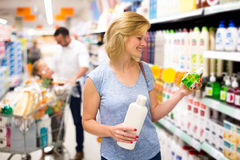 Клиент женщины выбирая шампунь Стоковое Фото