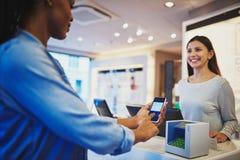 Клиент женщины наблюдая оплатить на регистре с телефоном стоковое фото