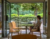 Клиент женщины ослабляет на таблице кафа на основаниях музея Rodin в Париже, Франции Стоковая Фотография
