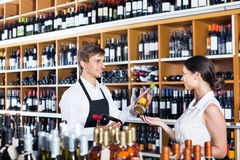 Клиент женщины порции продавца с бутылкой вина Стоковые Изображения RF
