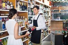Клиент женщины порции продавца с бутылкой вина Стоковые Фотографии RF