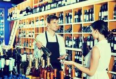 Клиент женщины порции продавца с бутылкой вина Стоковая Фотография