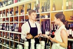 Клиент женщины порции продавца с бутылкой вина Стоковое фото RF