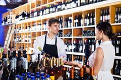 Клиент женщины порции продавца с бутылкой вина Стоковые Фото