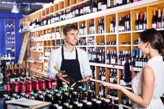 Клиент женщины порции продавца с бутылкой вина Стоковые Изображения