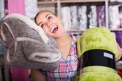 Клиент женщины смотря через покрывала в магазине ткани стоковые фотографии rf