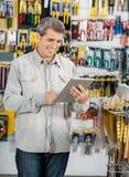 Клиент используя таблетку цифров в магазине оборудования Стоковое Изображение