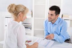 Клиент и советник сидя на столе говоря о выходе на пенсию ar Стоковые Изображения