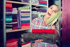Клиент молодой женщины выбирая различные полотенца Стоковые Фотографии RF