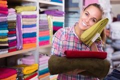 Клиент молодой женщины рассматривая различные полотенца Стоковое Изображение