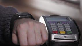 Клиент оплачивая с технологией NFC умным вахтой безконтактным на стержне в современном кафе сток-видео